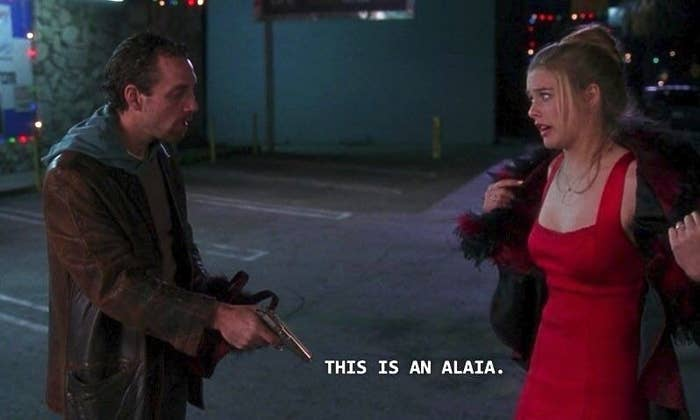 """A screenshot of from """"Clueless"""" of the scene where Cher is being mugged while wearing a red dress and says """"this is an Alaïa"""""""