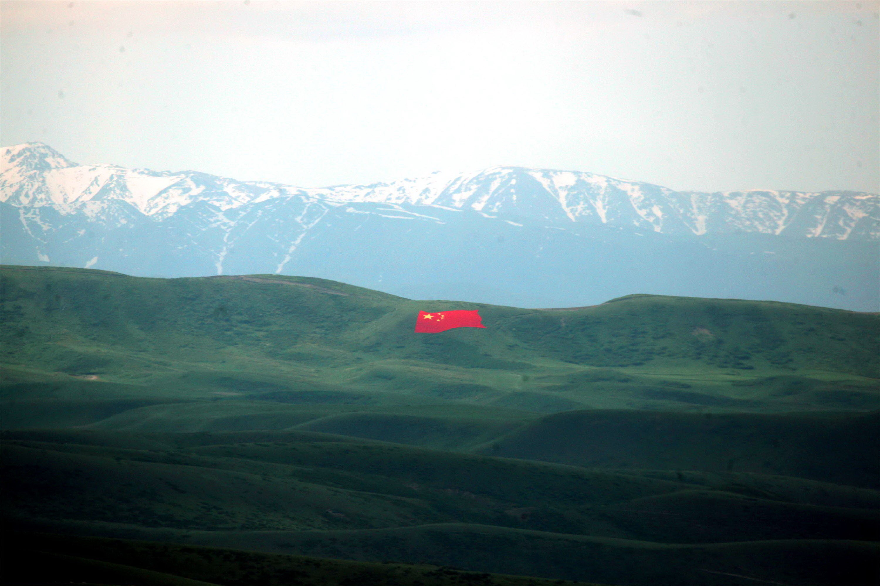 A massive Chinese flag which has been painted on a hill, with a large mountain range in the background