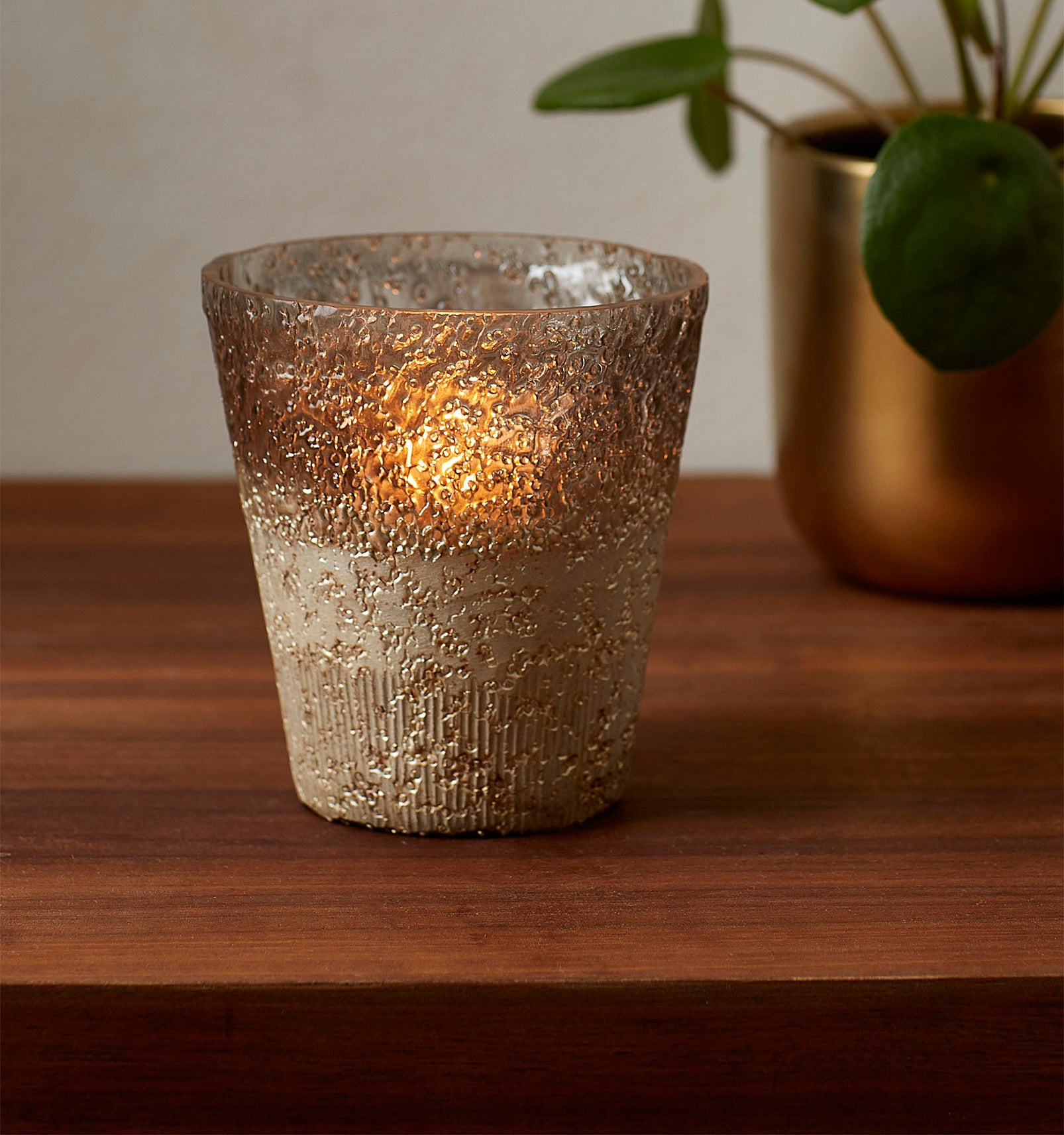 A candle votive is illuminated by a candle