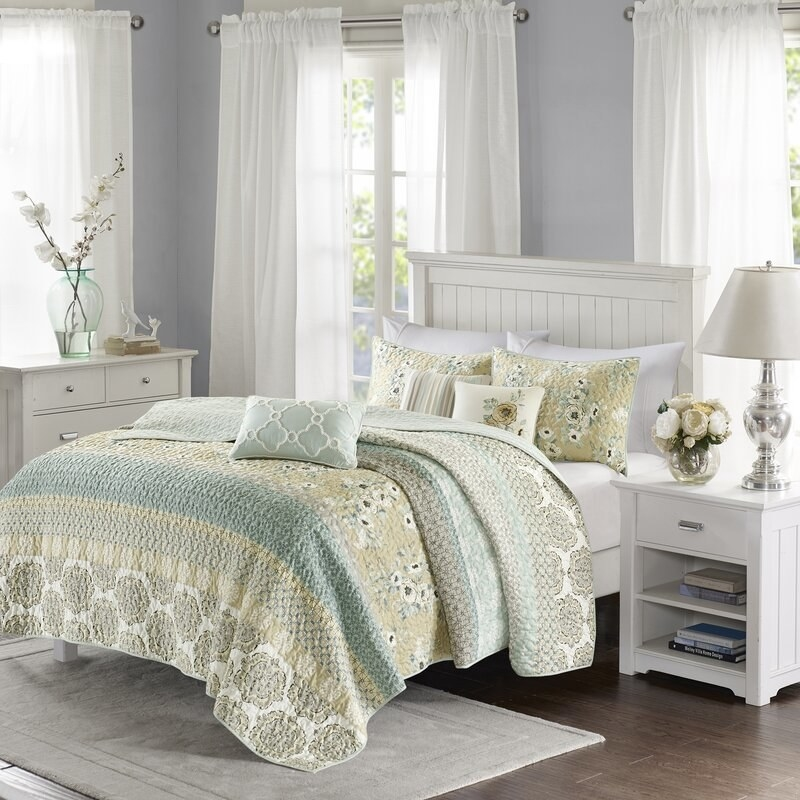 August Grove's Tappen reversible coverlet with a mix of abstract and floral patterns all in pastel colors