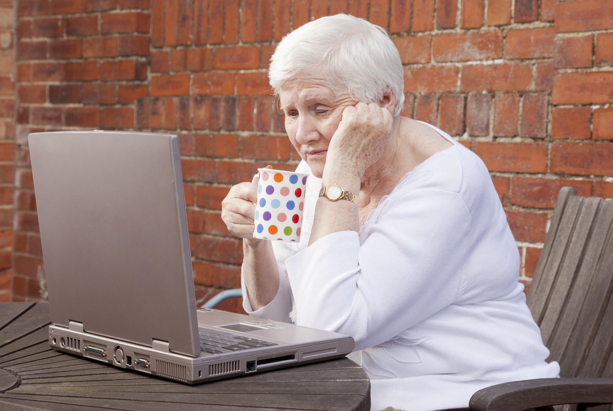 An old woman at a computer looking sad