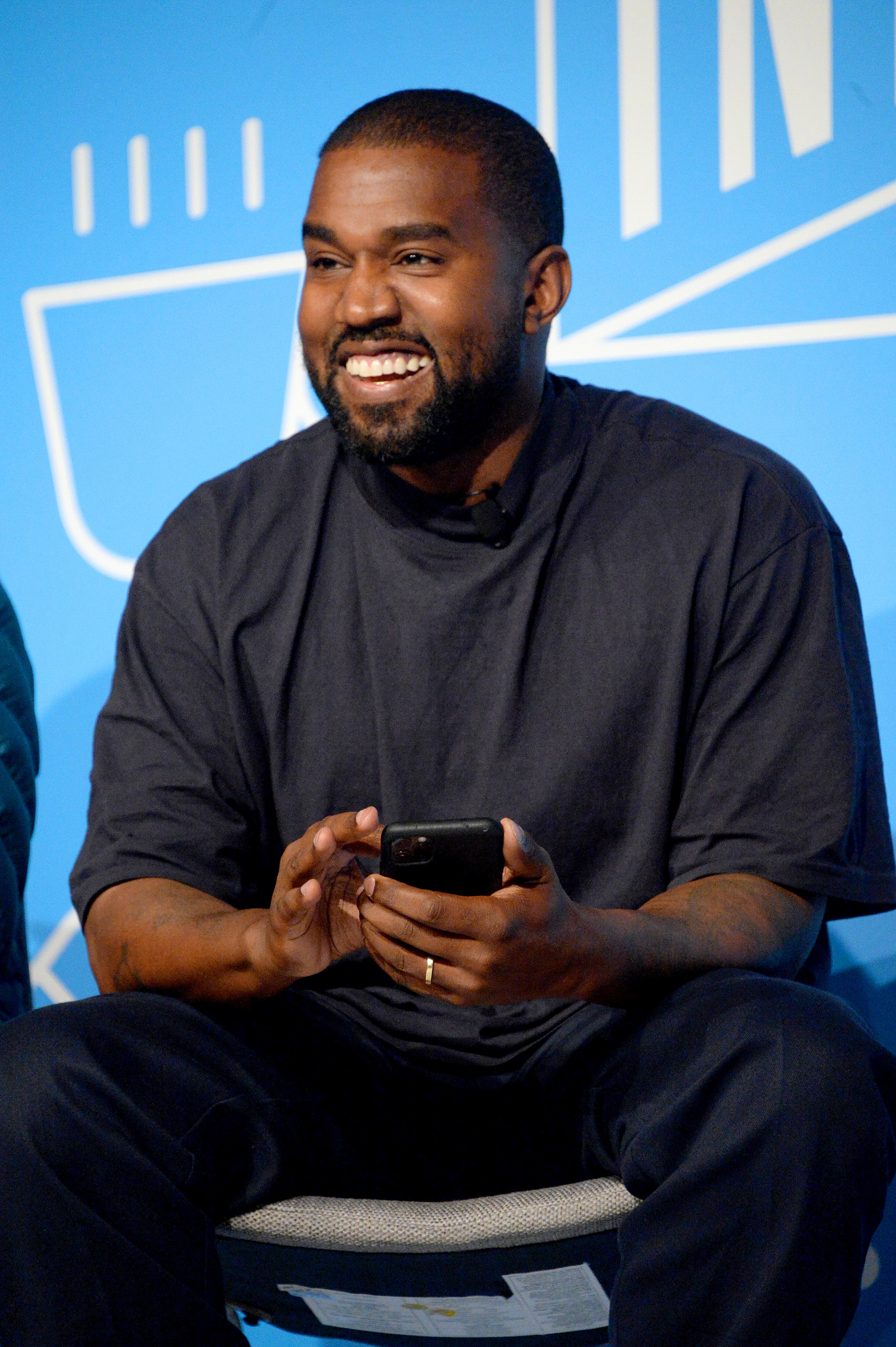 Kanye West smiles with his phone in his hand