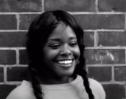Azealia Banks stands against a brick wall