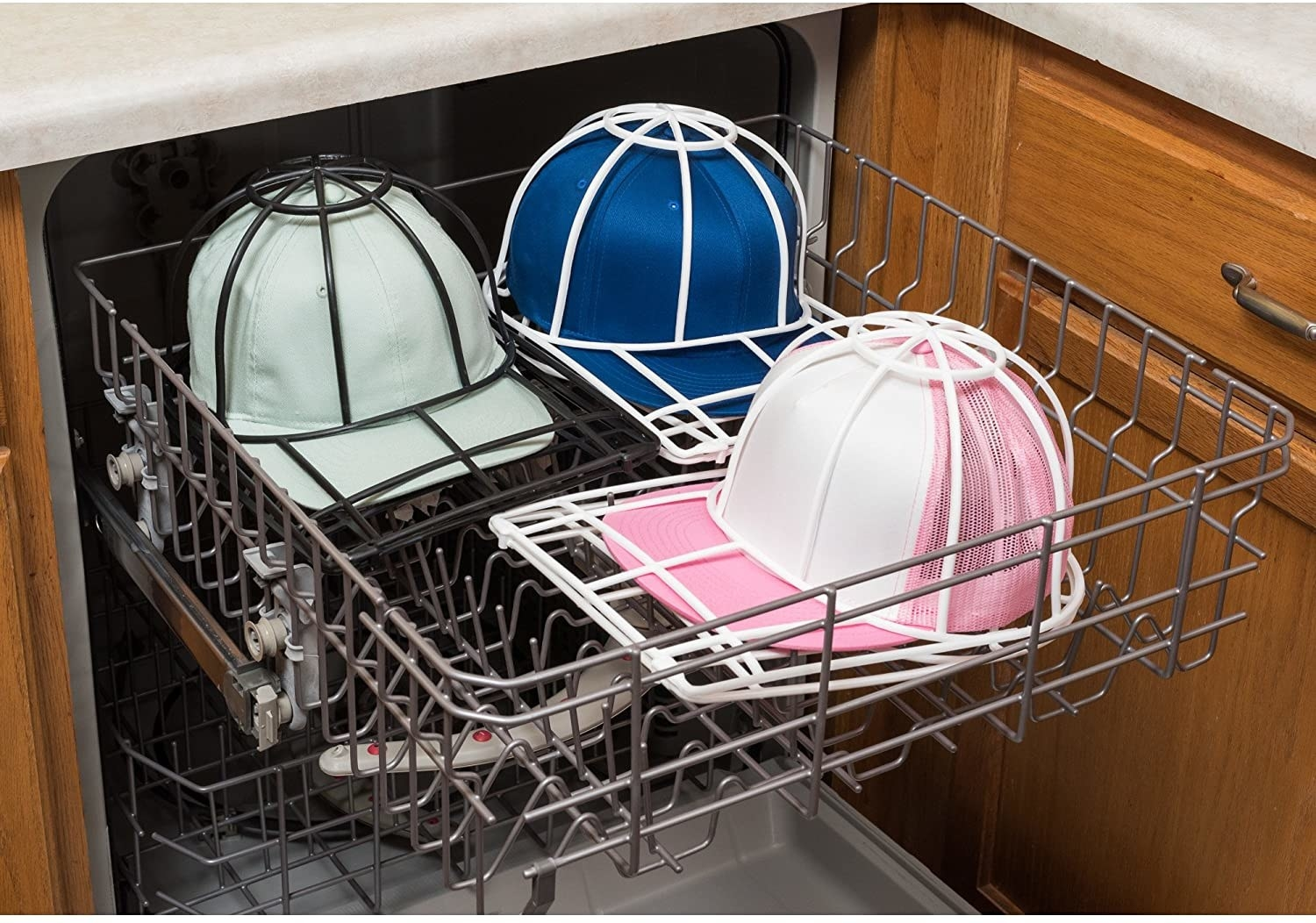 Three baseball caps in protective plastic cages sitting on the top rack of a dishwasher