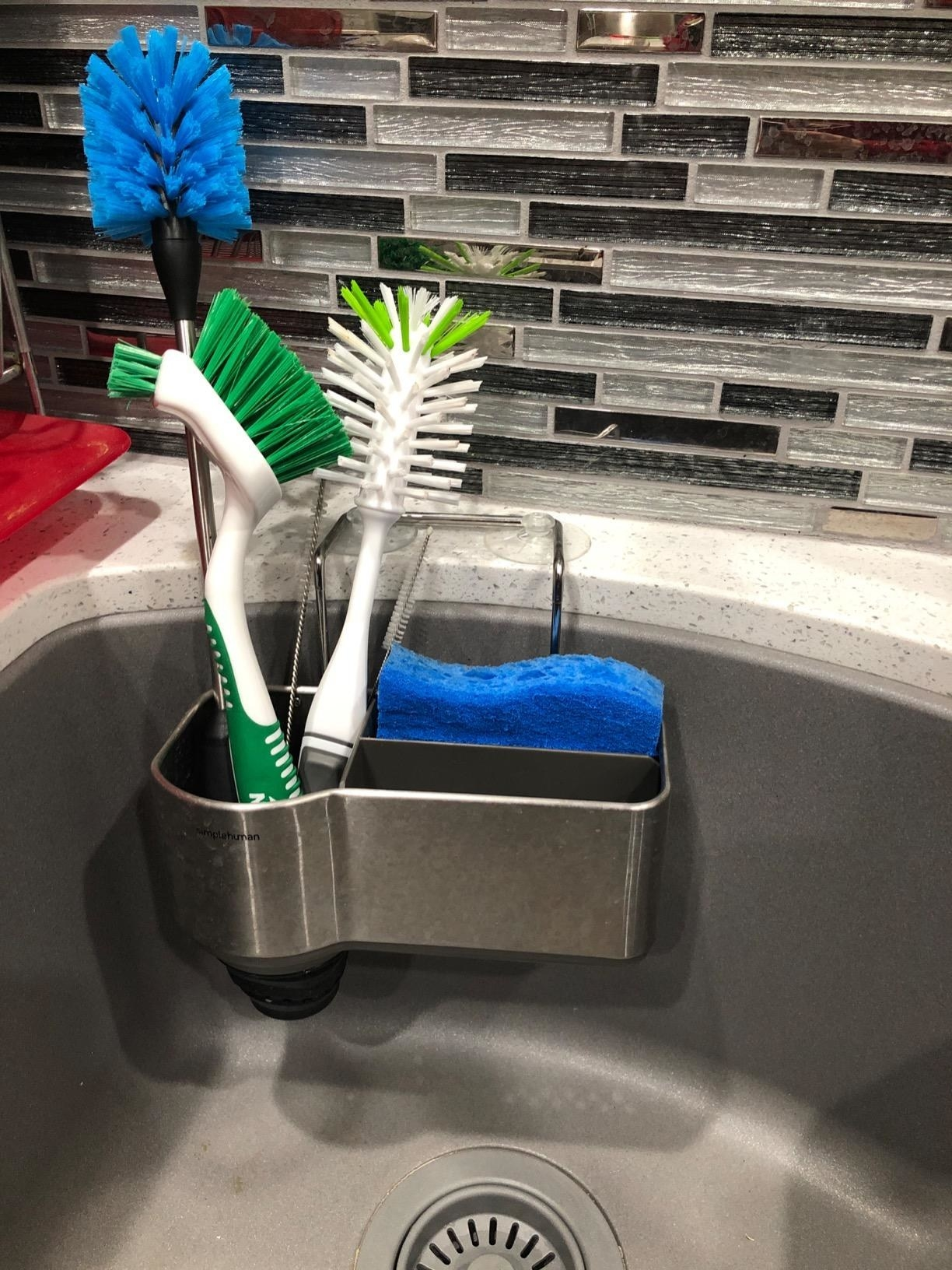 Sink caddy attached to the side of a sink with brushes and sponge inside