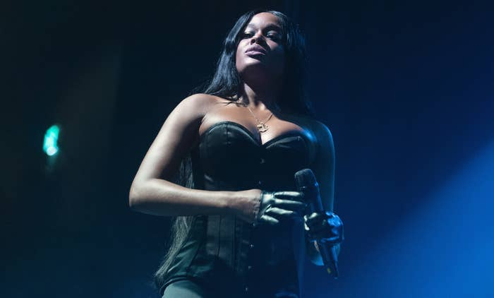 Azealia Banks stands onstage by a blue light wearing a black corset top and holding a microphone