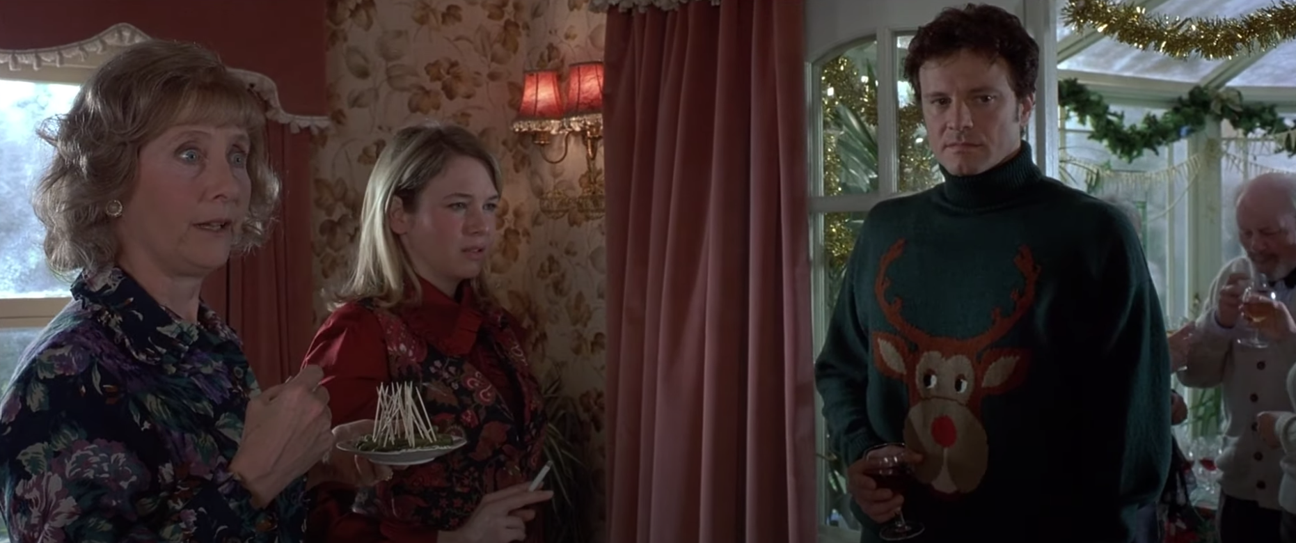 """Bridget, her mother, and Mark stand together at a holiday party in """"Bridget Jones's Diary."""""""