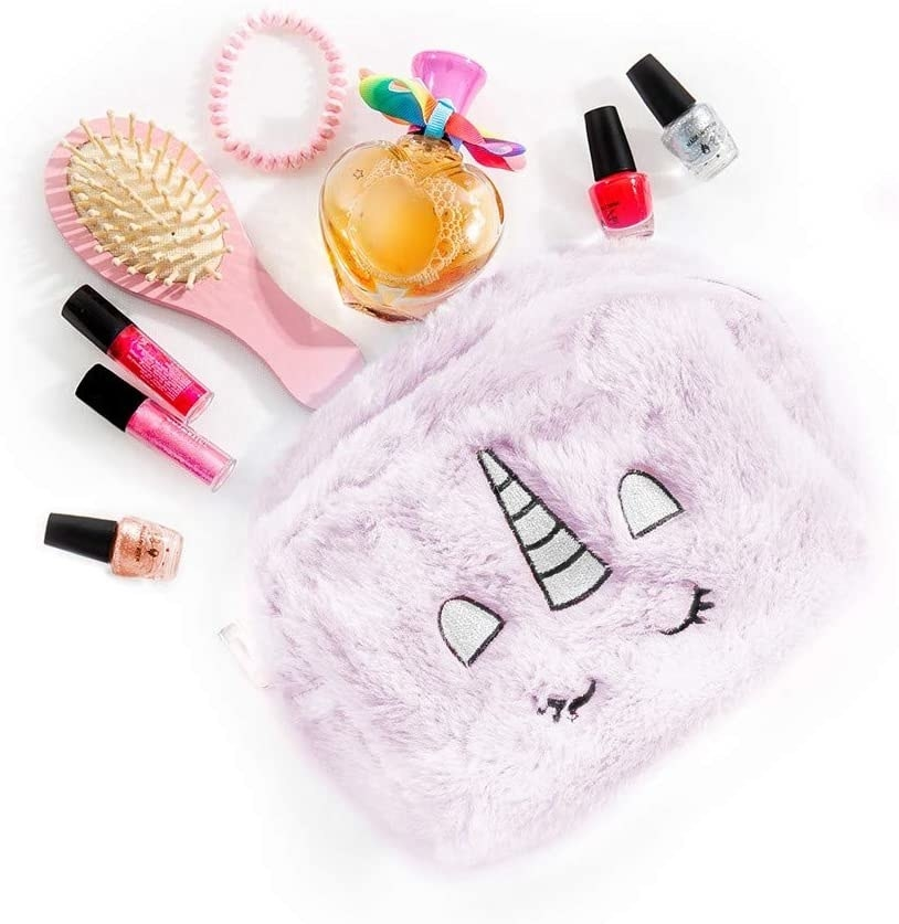 A fluffy bag with unicorn features and beauty products around it