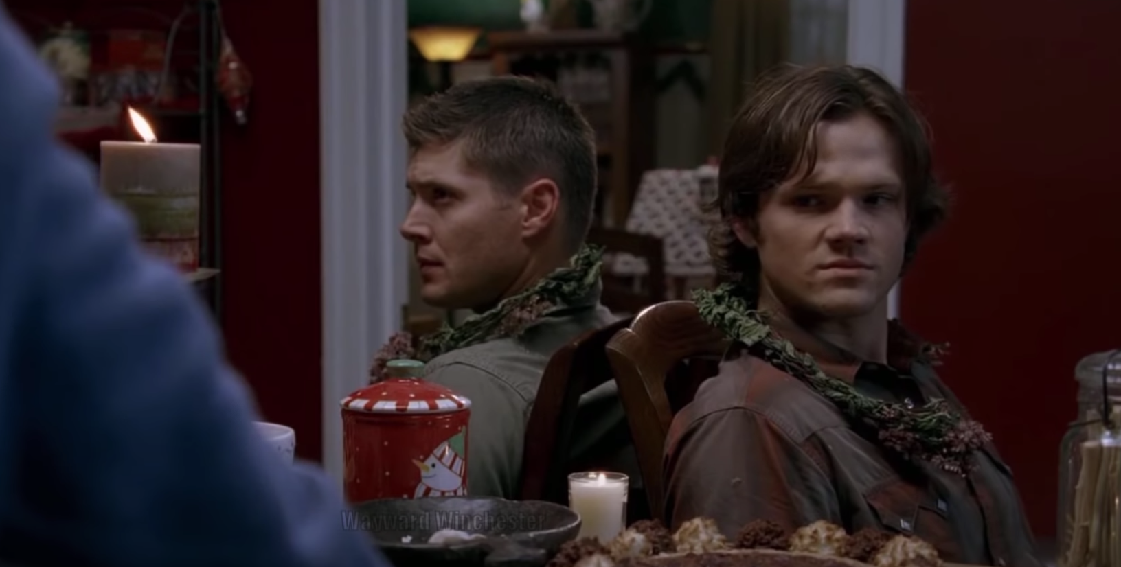 """Sam and Dean sit in a kitchen while they are tied up with garland on """"Supernatural."""""""