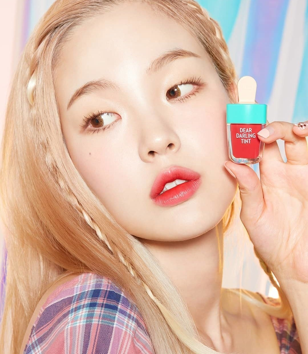 A person holds a lip tint that looks like a popsicle with a tint on their lips