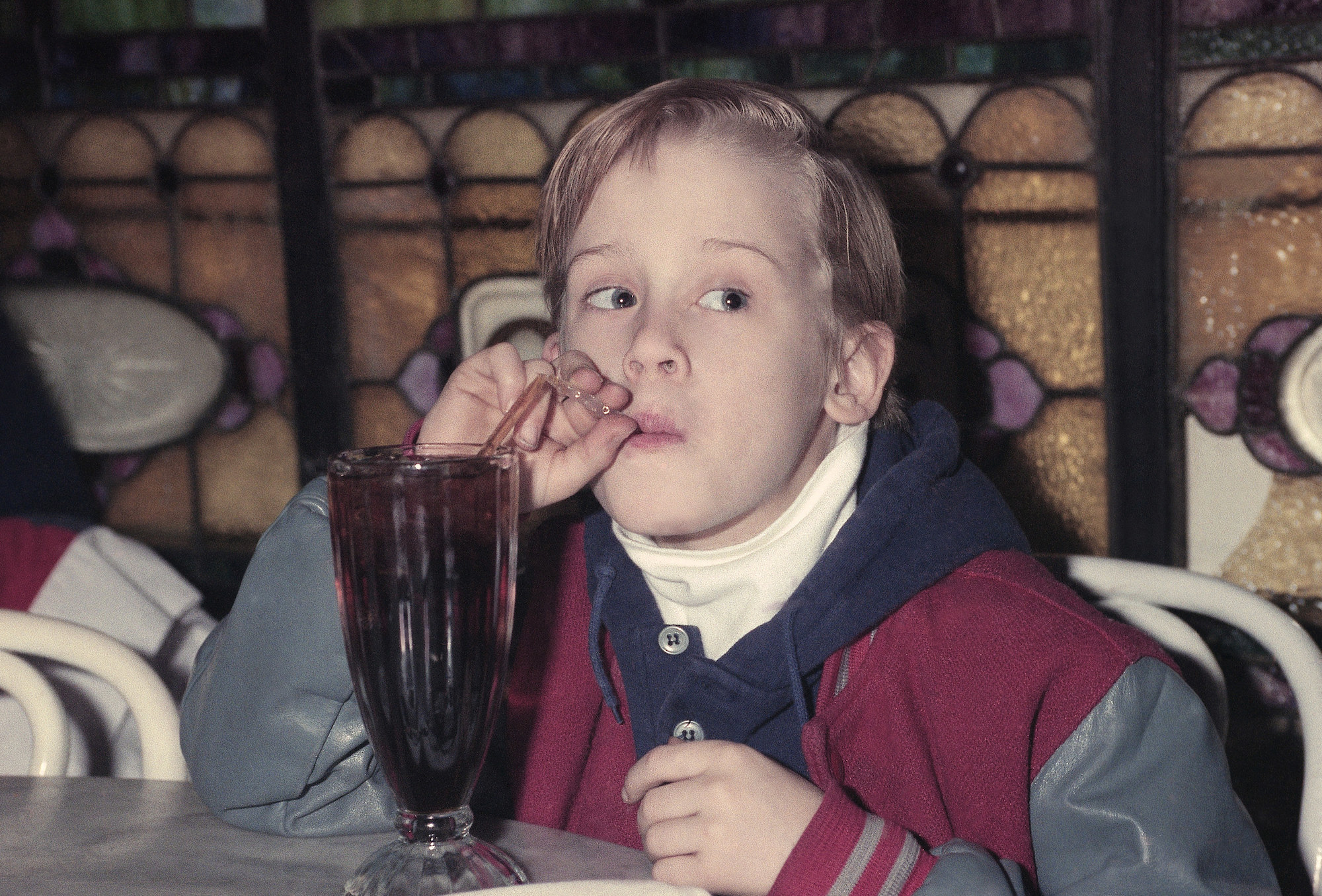 Macaulay drinking a soda as a kid