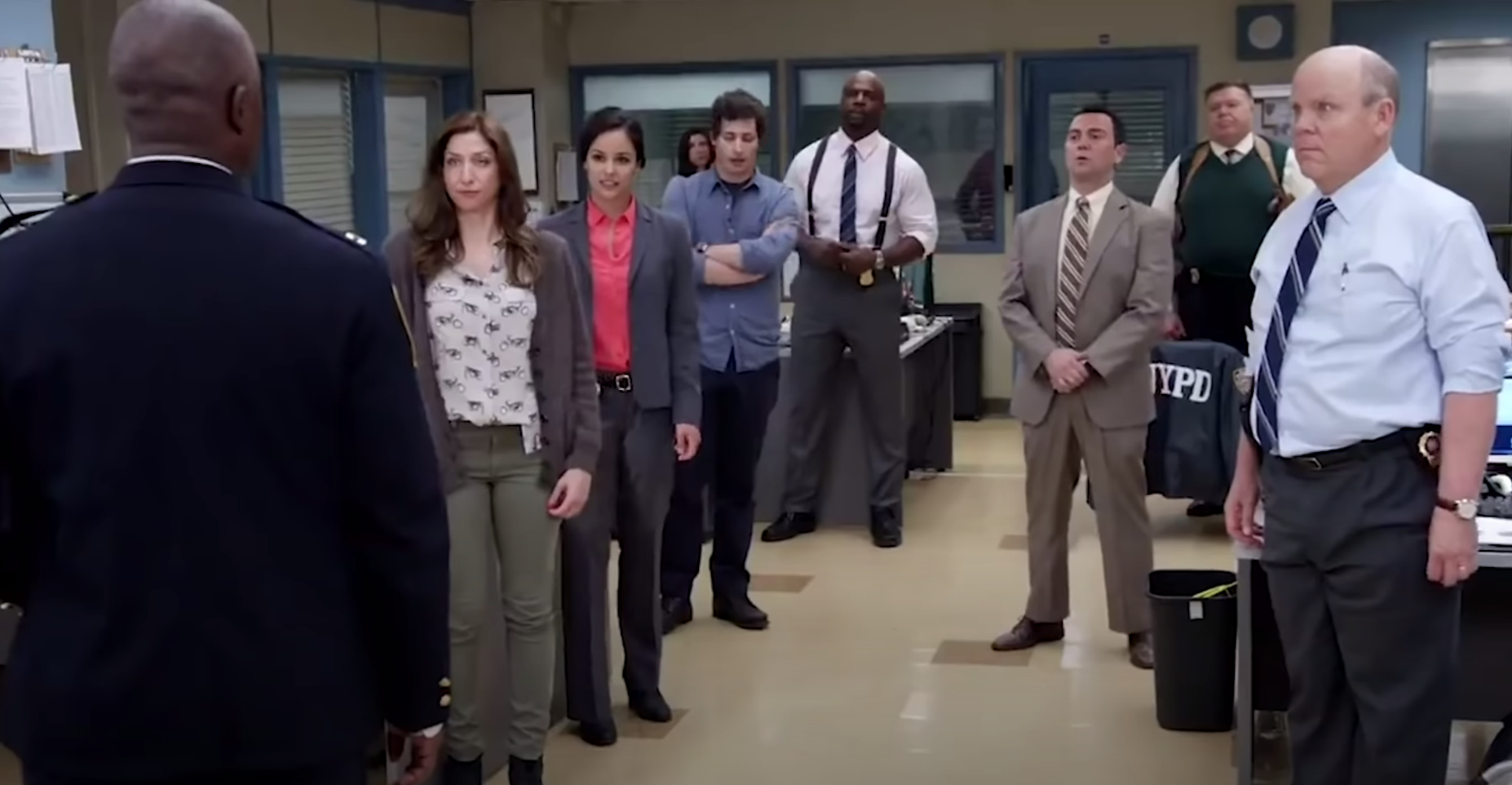 "The ""Brooklyn Nine-Nine"" team stands and listens to Captain Holt."