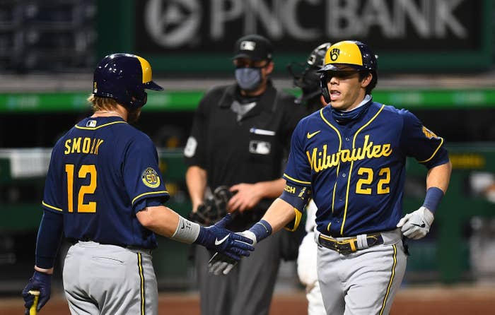 Two Milwaukee Brewers players high-five during a game