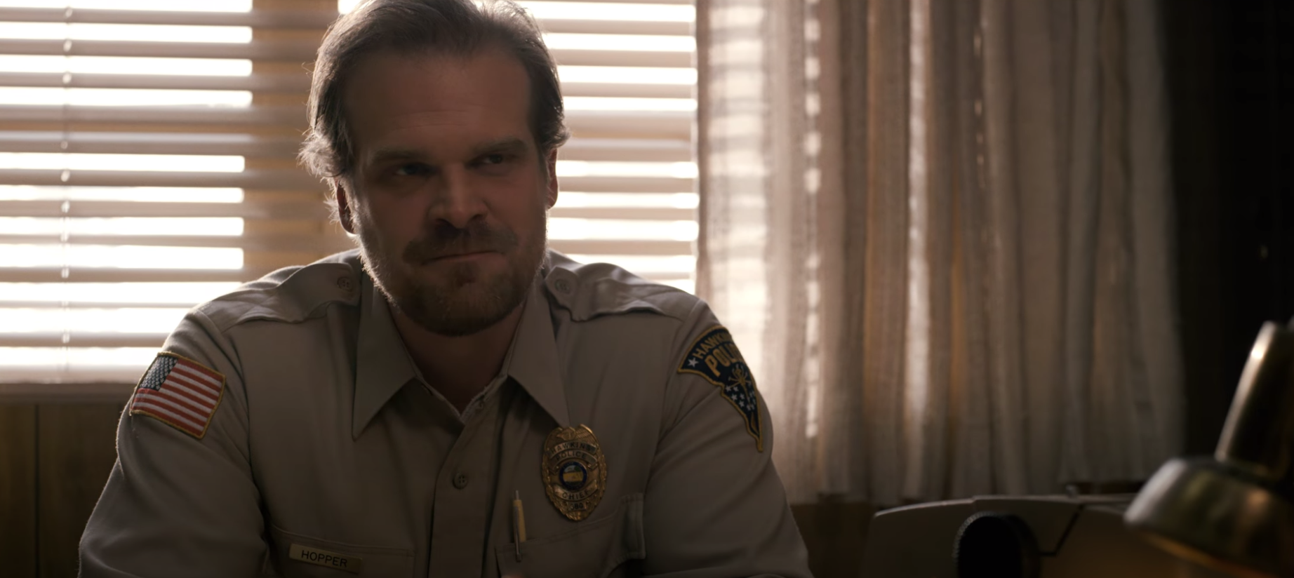 """Hopper sits at his police chief desk while wearing the uniform in """"Stranger Things."""""""