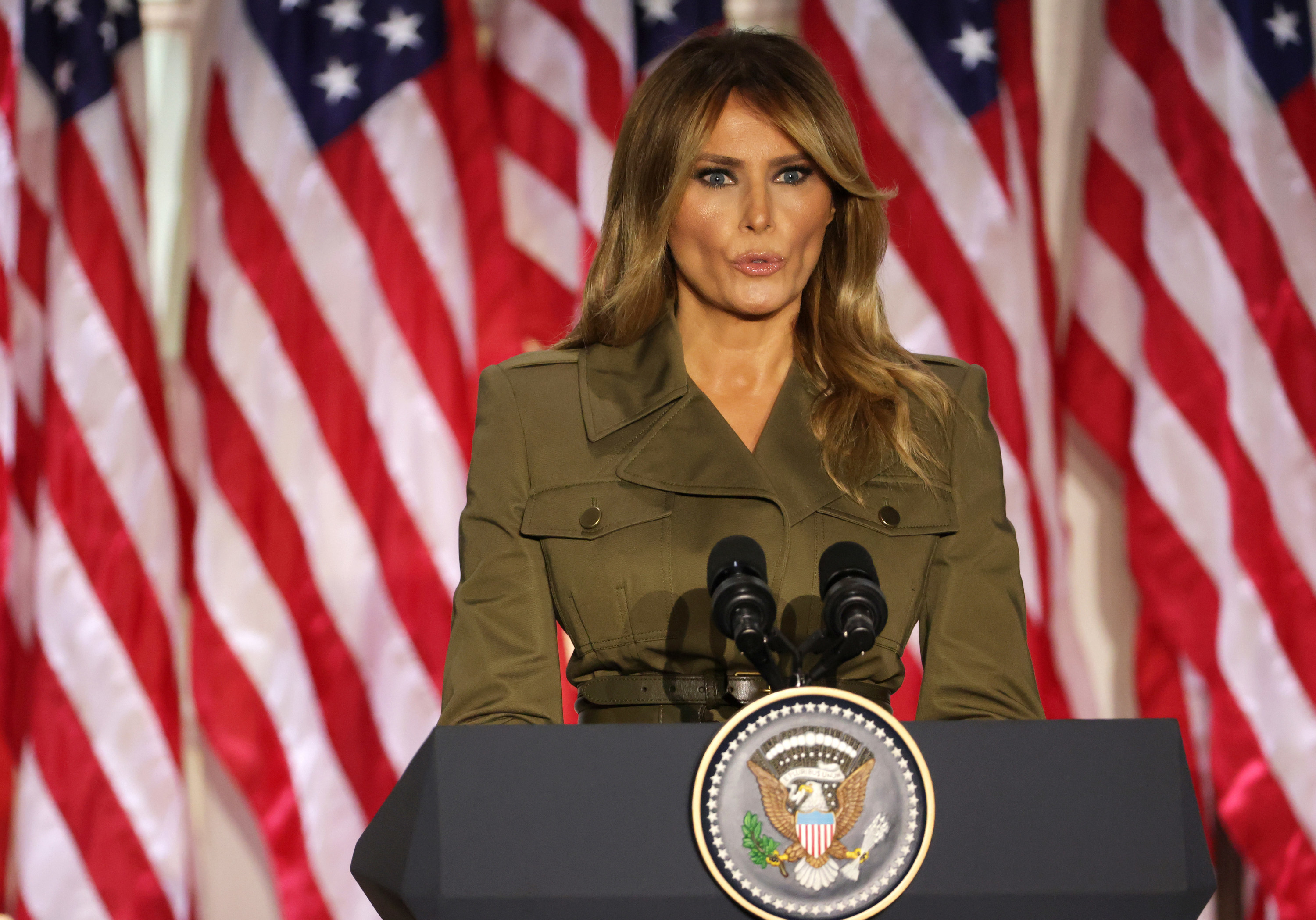 Melania Trump speaks from behind a lectern with the presidential seal on it