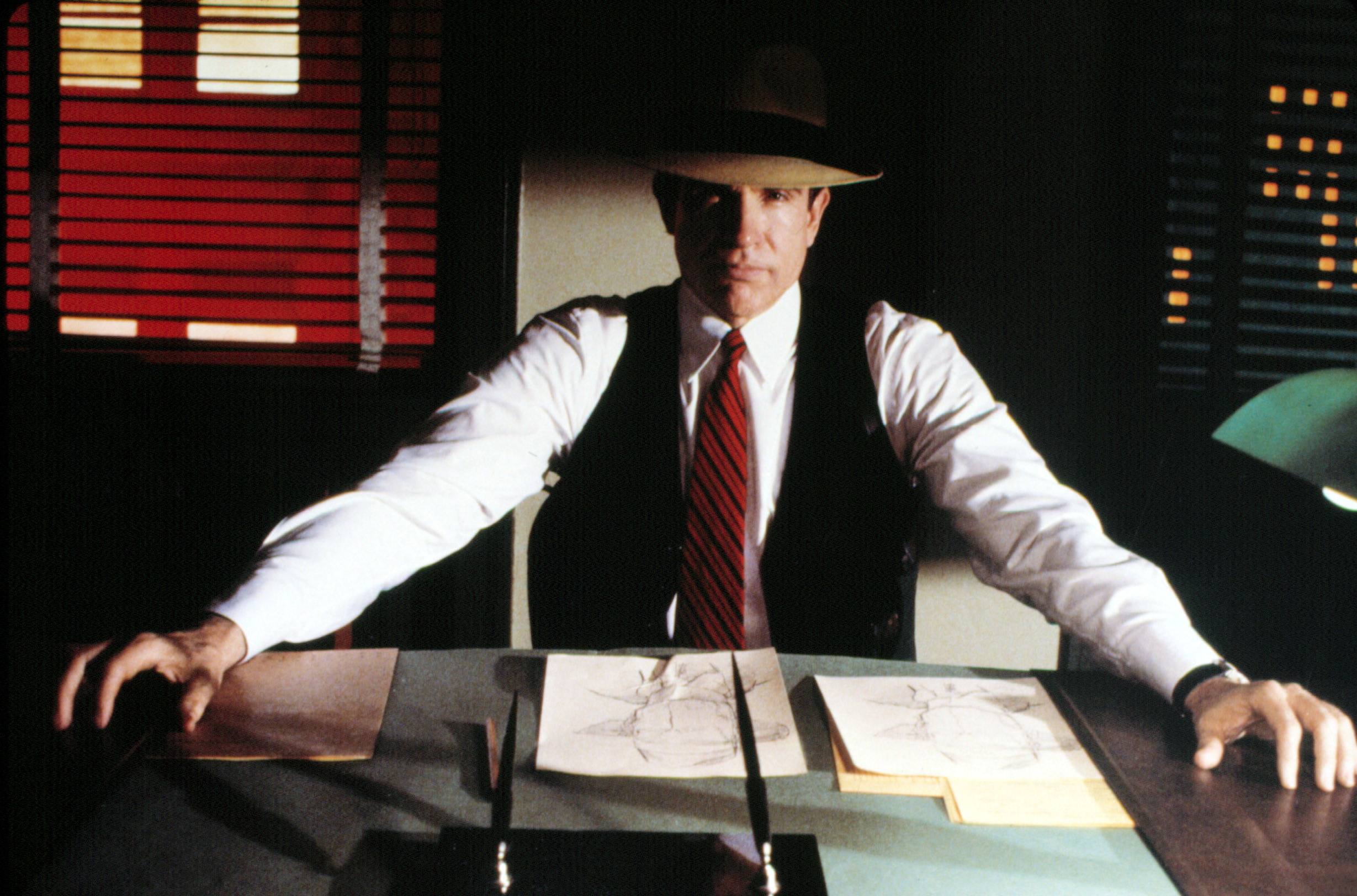 A promotional photo of Warren Beatty as Dick Tracy sitting at his desk looking stern face