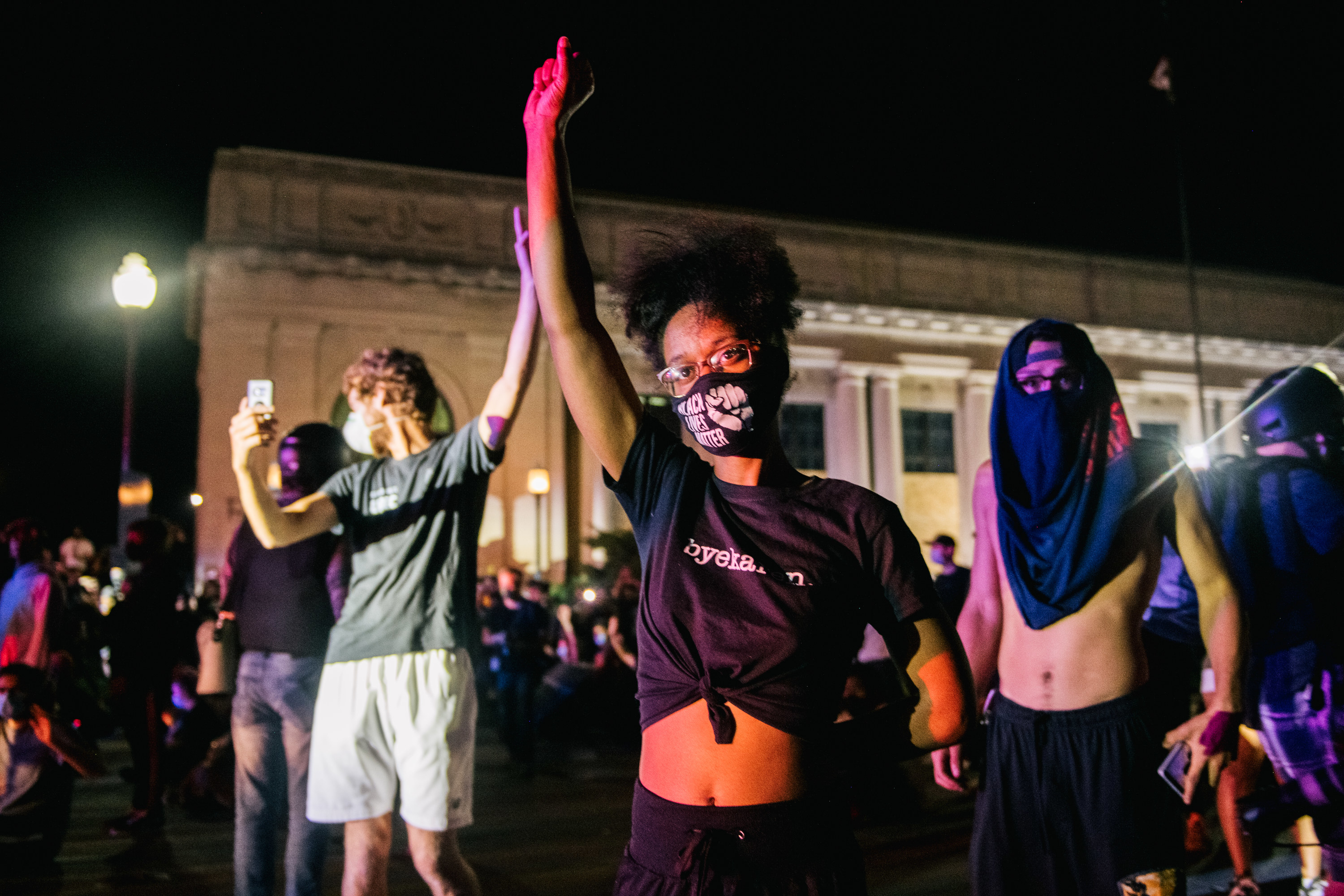 """A Black woman, wearing a tied-up black T-shirt and face mask that reads """"Black Lives Matter,"""" holds up her fist and looks into the camera"""