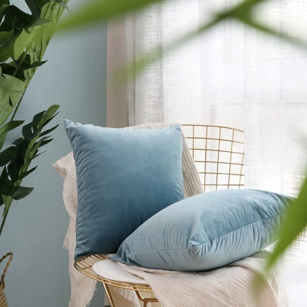 Two pillows with blue velvet pillowcases sitting on a chair