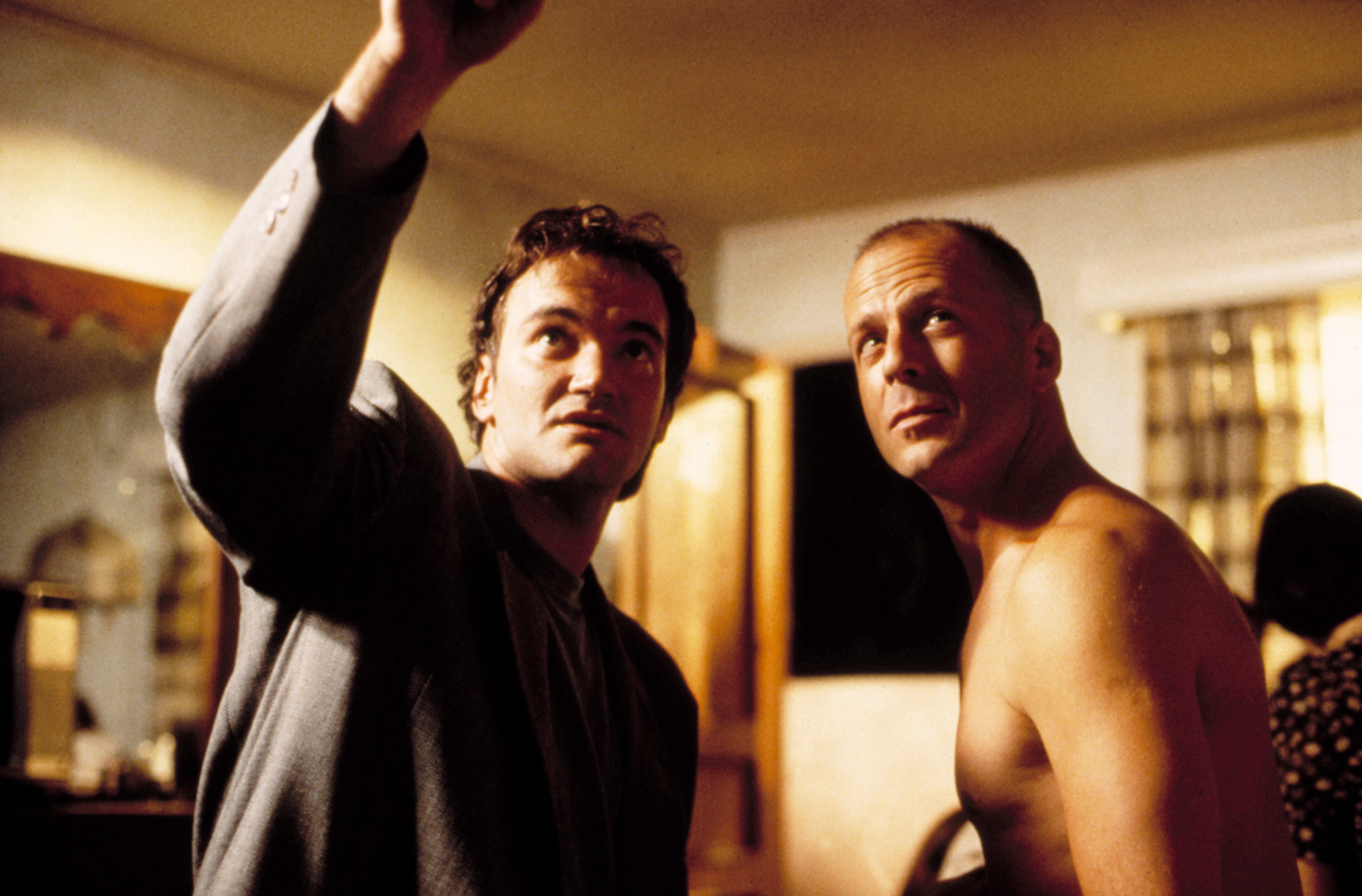 """A behind-the-scenes photo of Quentin Tarantino directing Bruce Willis on the set of """"Pulp Fiction"""""""