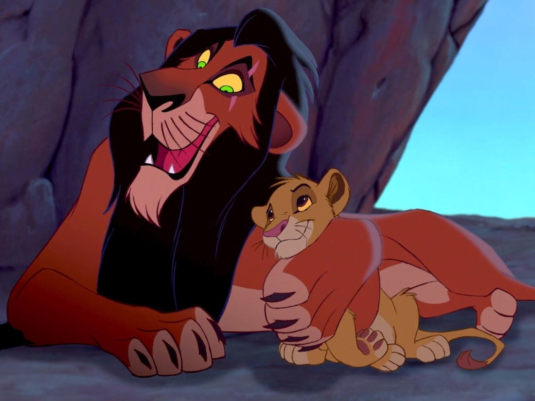 A screenshot of Scar hugging a young Simba in his cave