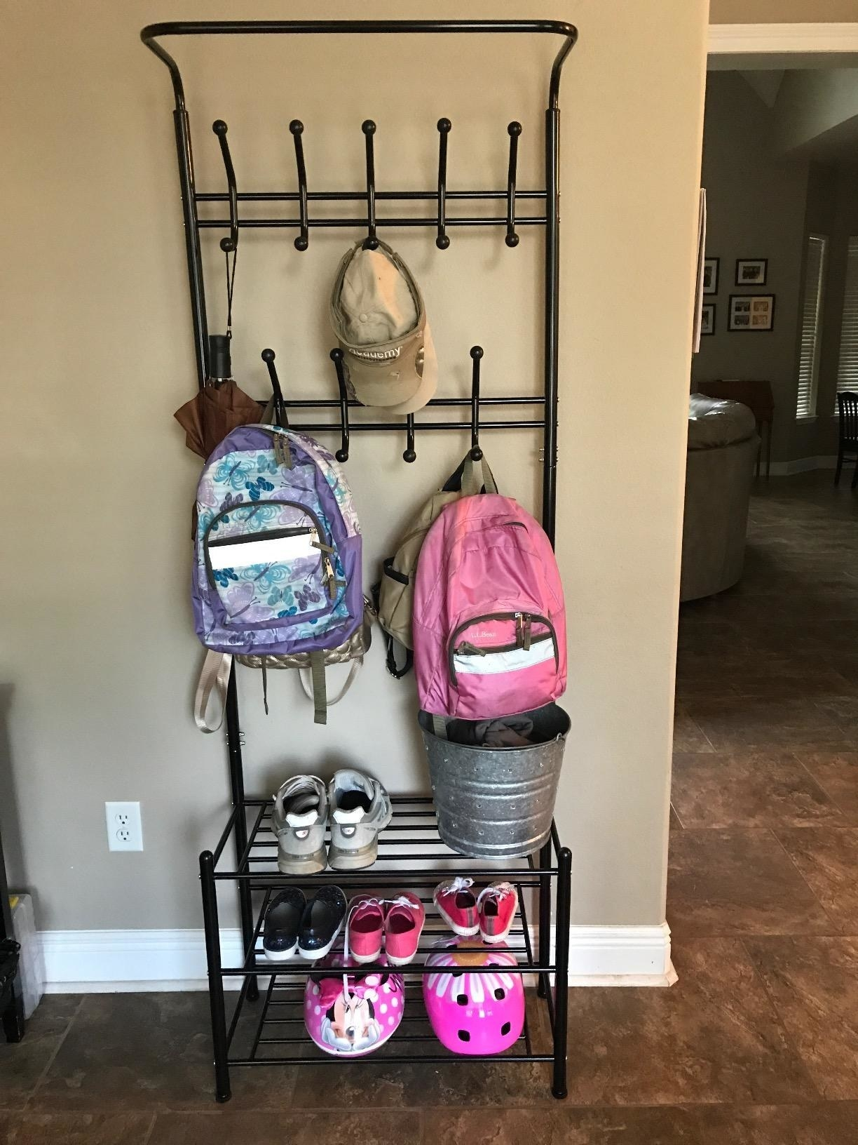 Reviewer pic of the black metal coat and shoe rack with assorted backpacks on the hooks and assorted shoes and helmets on the three racks