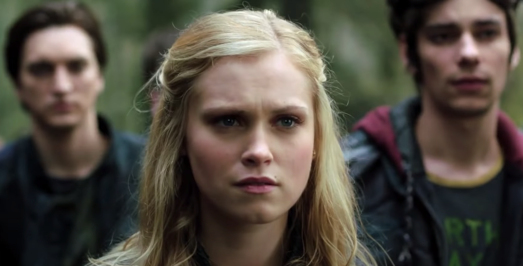 "Murphy, Clarke, and Jasper stand on earth with concerned looks in ""The 100."""
