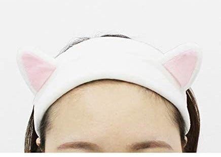 A person wears a headband with cat ears to keep their hair from their face