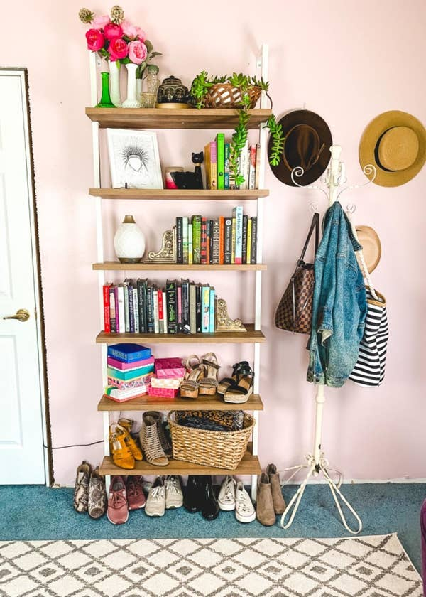 Reviewer pic of the six-tier bookshelf with light brown wood shelves and white rods attached to the wall with books and trinkets on the top four shelves and assorted shoes and accessories on the bottom shelves