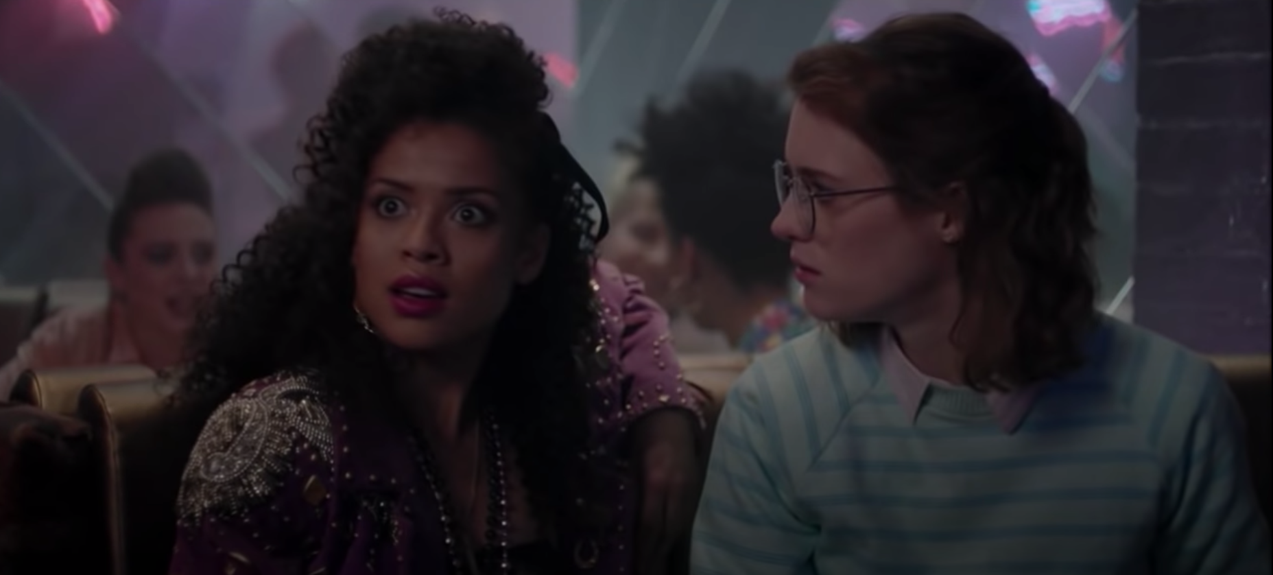 "Kelly and Yorkie sit in a club with shocked faces in ""San Junipero."""