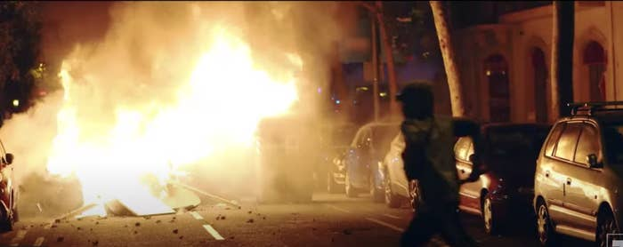 Person running near a fire set in the streets of Barcelona in 2019.
