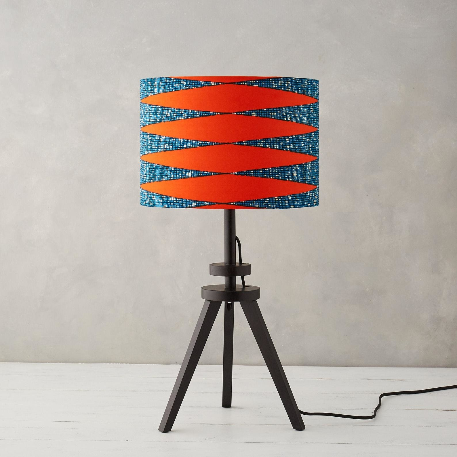 a circular lampshade with bright orange and blue print on it. the lampshade is on a black  tripod-style lamp.