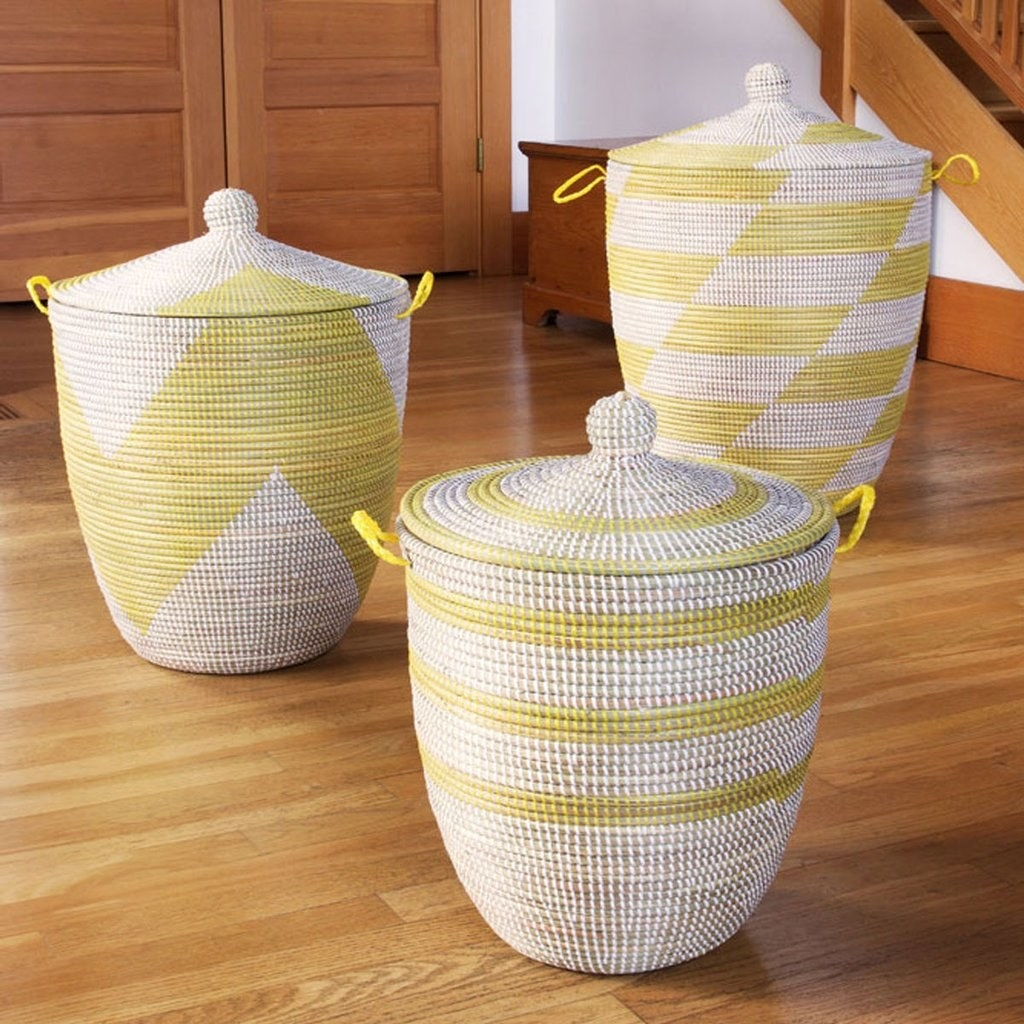 Three baskets in white and yellow patterns with lids that have a small handle in the middle; the largest one has a checkerboard pattern, the medium one a chevron, and the small one stripes