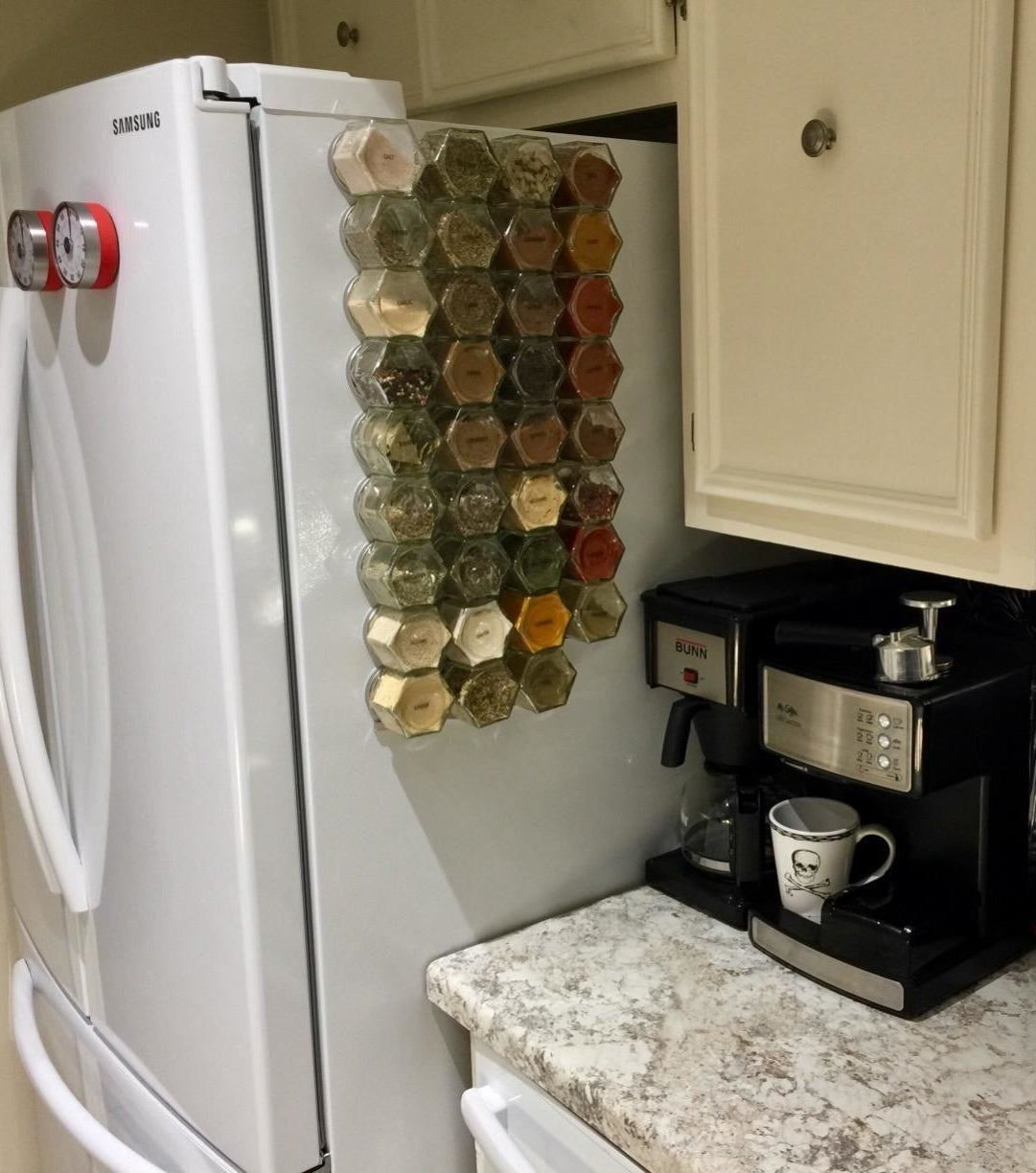 Reviewer pic of a number of glass spice jars stuck to the side of a fridge