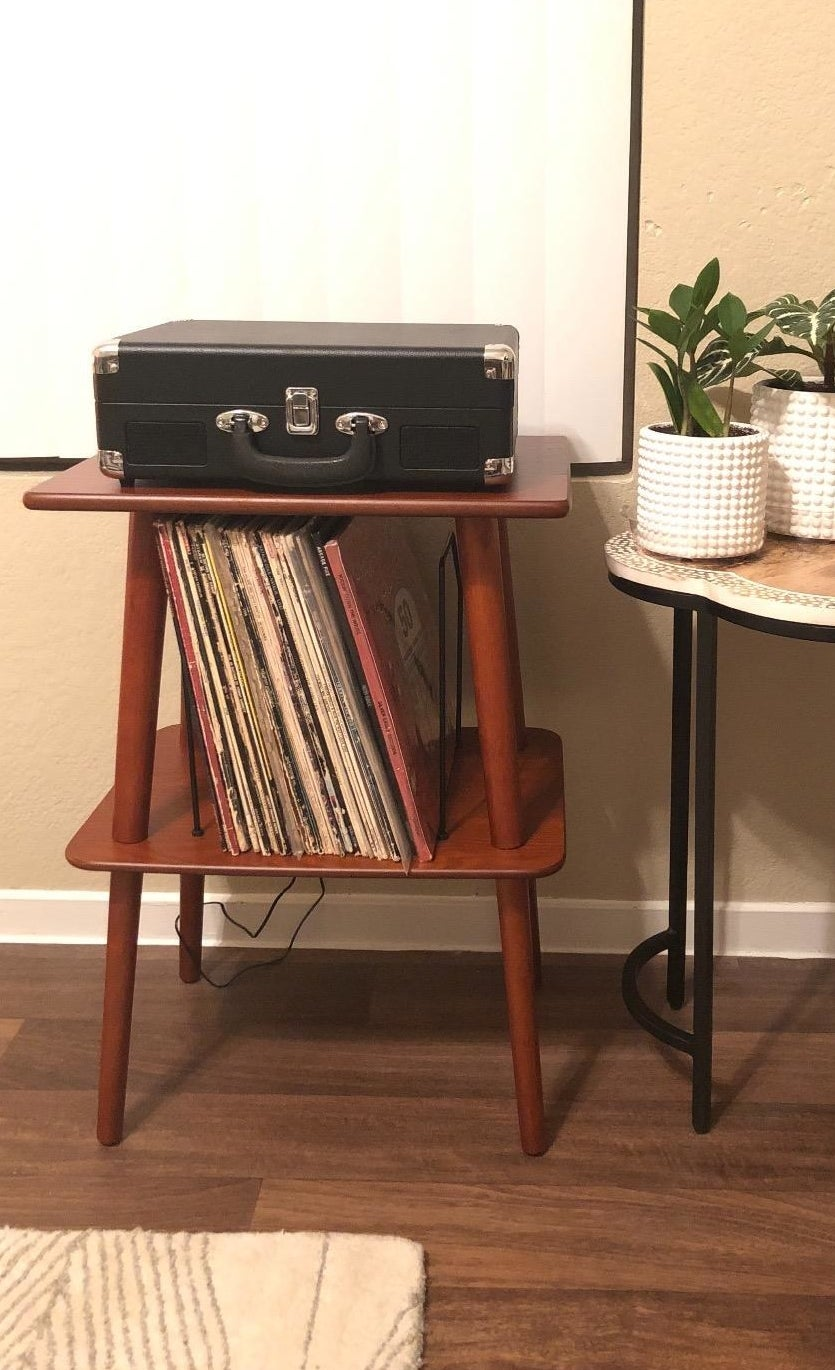 Reviewer pic of the brown wood two-tier stand with black wire slots in the middle holding vinyl records and a record player on top
