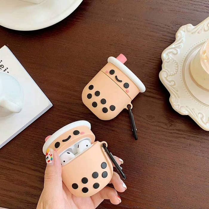 hand holding the boba tea case which is light brown like the tea and has little black circles at the bottom that look like the bubbles. It also has a pink faux straw coming out of the top