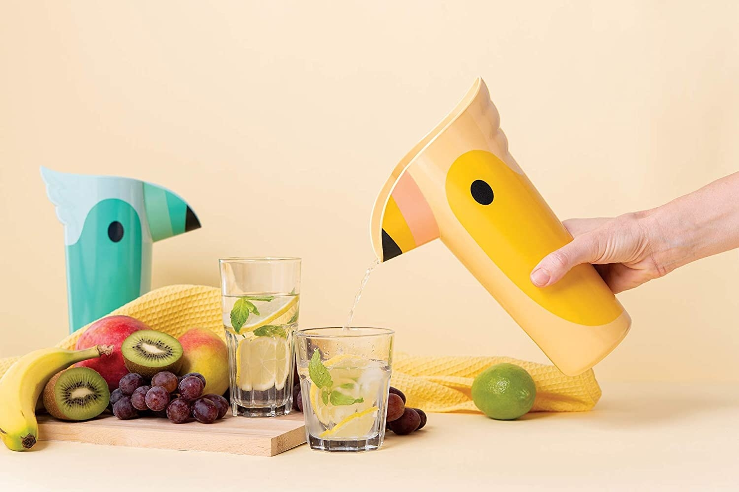 model's hand holding the yellow toucan pitcher which has lemonade coming out of it that's going into a glass. There's a turquoise pitcher also sitting next to another glass.