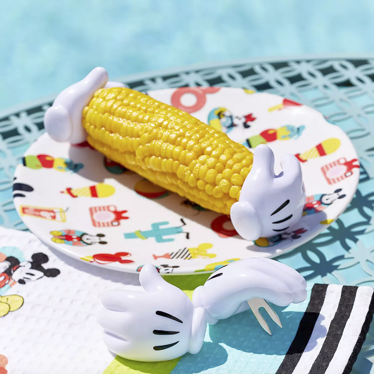 two corn holders attached to both ends of an ear of corn on a plate and two additional holders sitting beside the plate