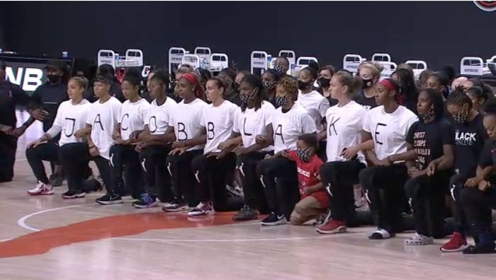 "WNBA players kneel in a row, each wearing a white T-shirt with a letter on it, spelling out ""Jacob Blake"""