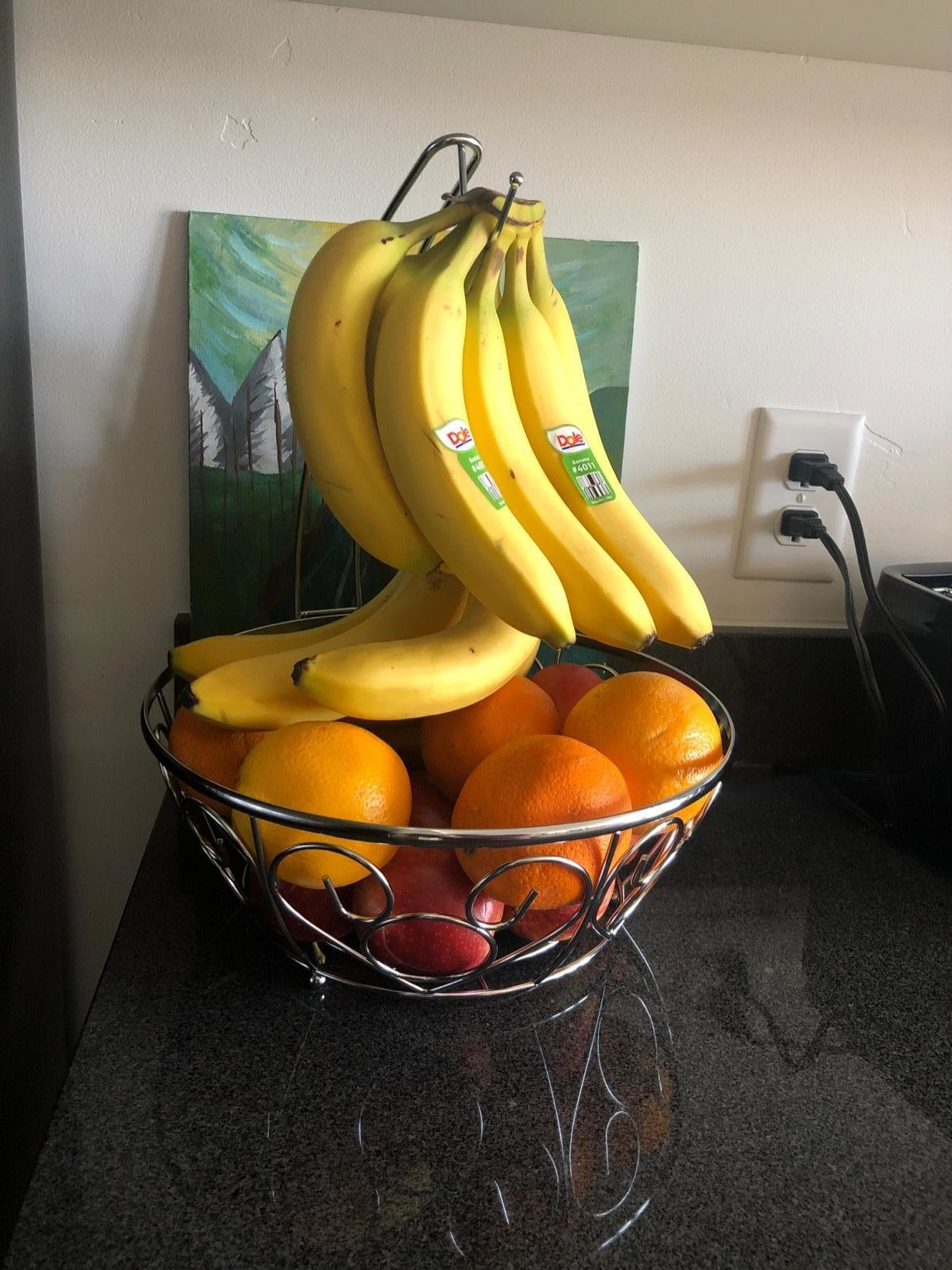 A chrome finish fruit basket filled with oranges and apples with bananas hanging  above