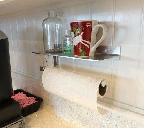 Aluminum paper towel holder with small shelf mounted to wall