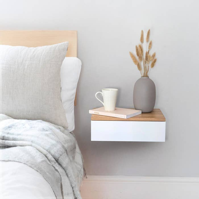 Rectangle white wood drawer with a light brown wood top attached to the wall next to the bed with a book, coffee cup, and vase on it