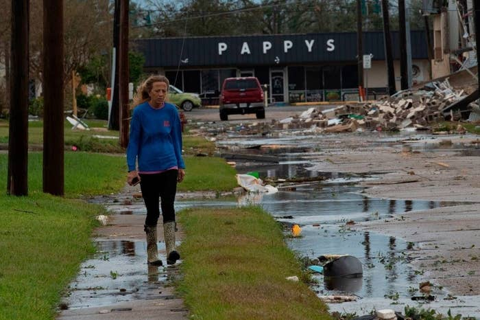 A woman walks down the wreckage of a street hit hard by Hurricane Laura in Lake Charles, Louisiana.