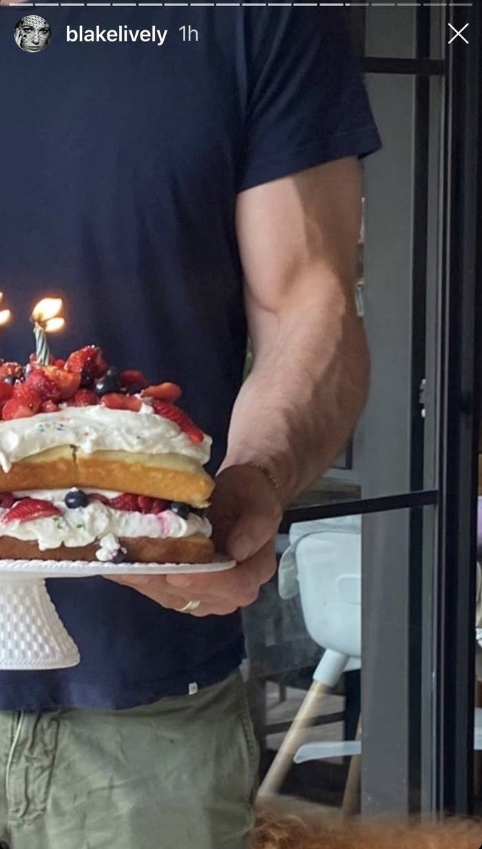 A zoomed-in version of the cake photo, zoomed in on Ryan's muscular bicep holding the cake