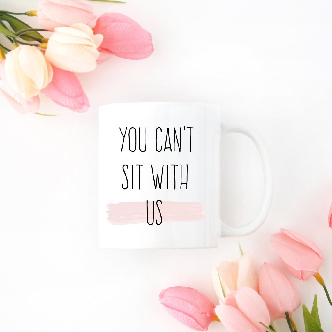 A coffee mug with You can't sit with us written on the front
