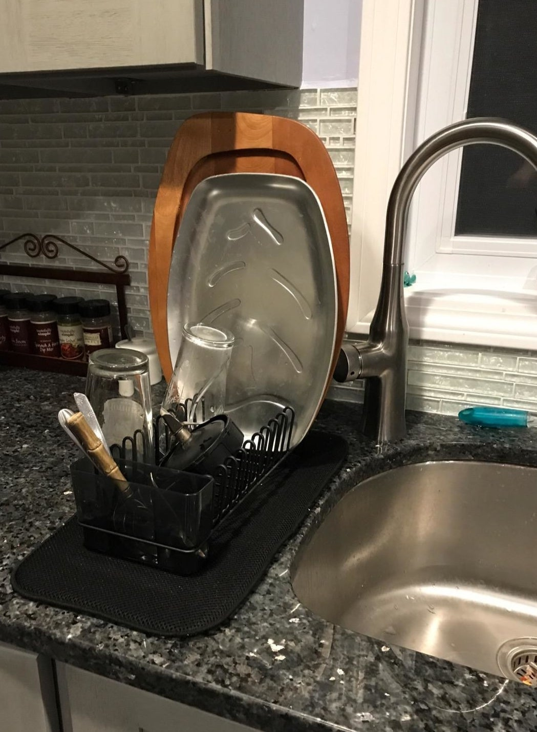 Reviewer picture of the small dish drying rack with the black mat under it with assorted dishes in it next to a sink