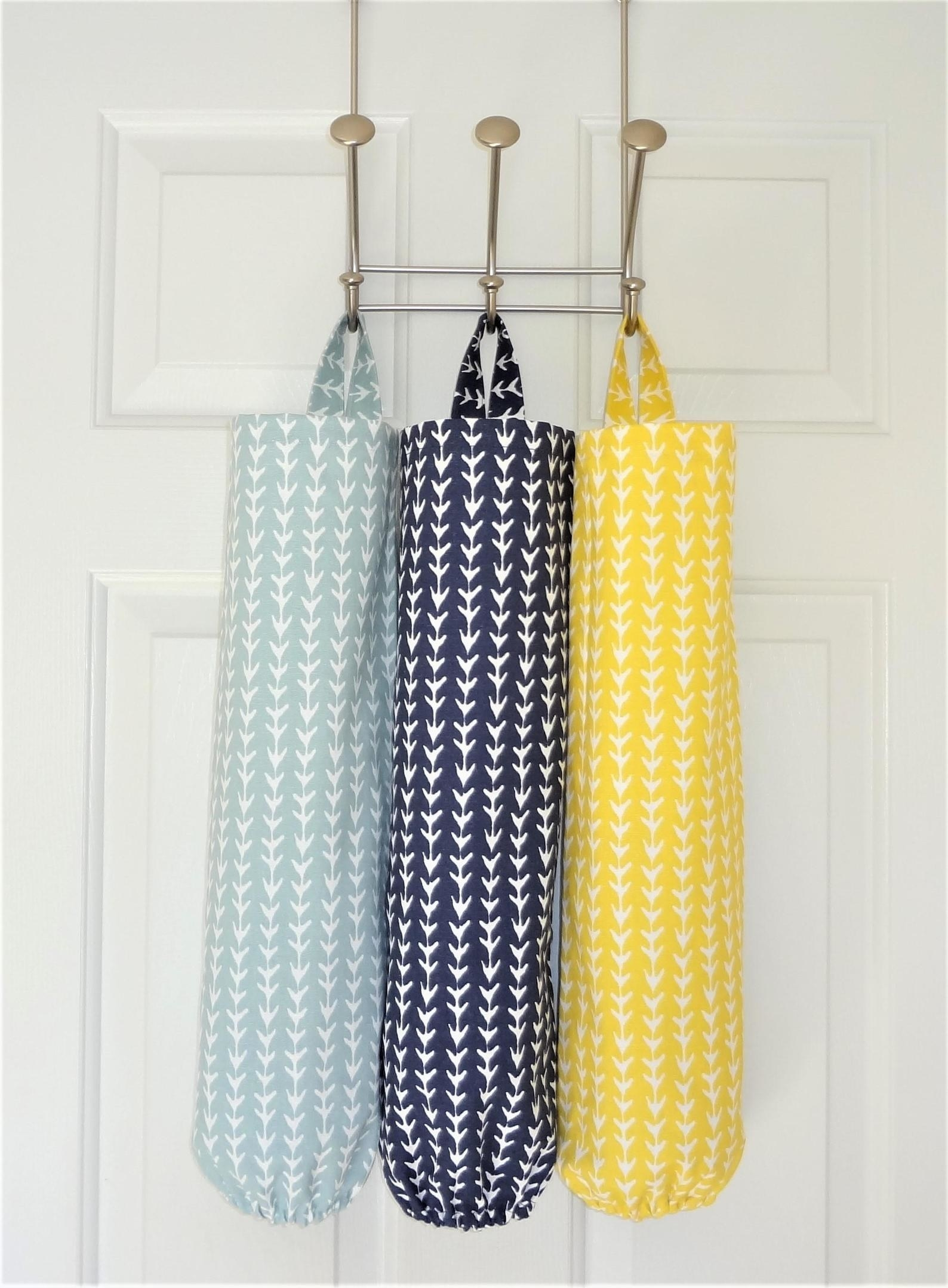 Light blue, navy, and yellow bag holders hanging from hooks on a door
