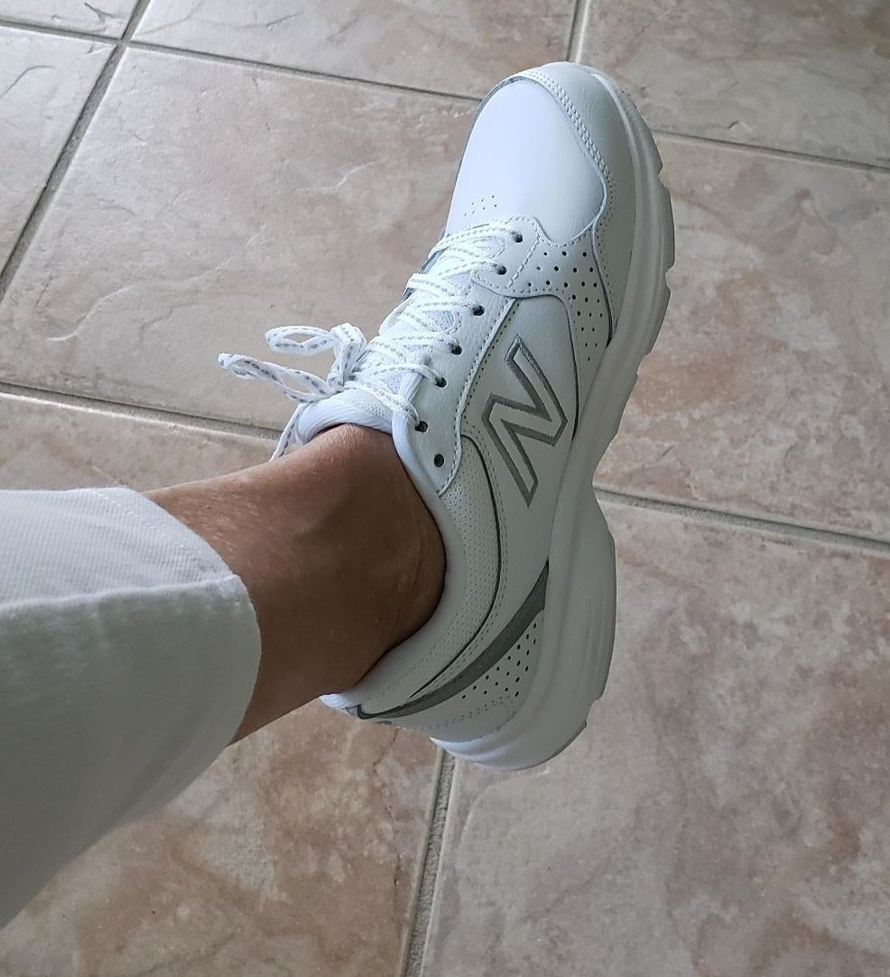 A reviewer showing the white New Balance sneaker with gray accents on their foot
