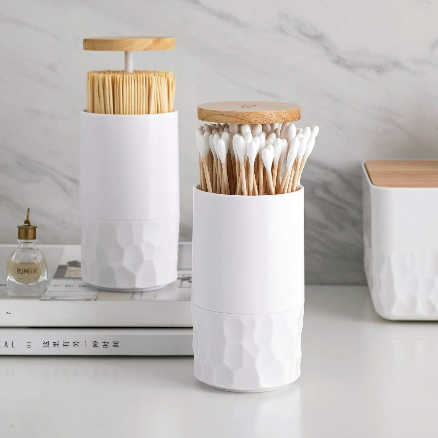 White upright jar with textured base and wooden push top with q-tips in it