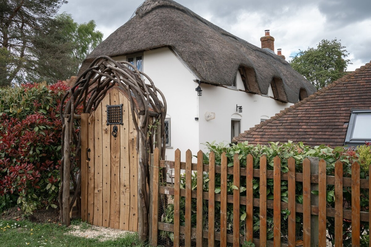 A wooden door framed with an arch made of tree branches stands in front of an old English-style cottage with a straw roof.