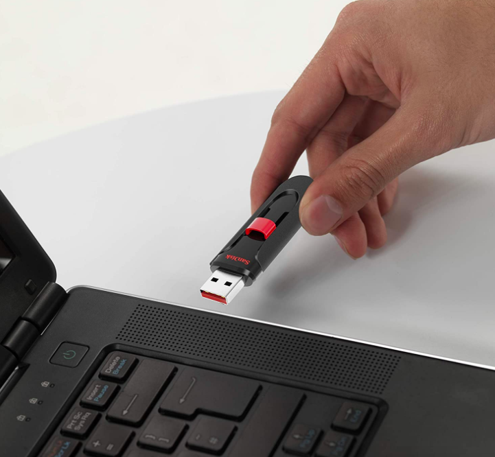 Hand holds black and red compact flash drive next to a black laptop
